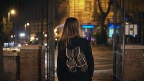 有背包的旅游妇女后走通过黑暗的公园的后面观点的在路附近在单独晚上 免版税图库摄影
