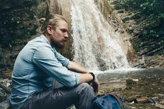 有背包的旅游旅客坐岩石临近远足目的地经验生活方式概念的瀑布艰苦跋涉 免版税图库摄影