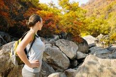 有背包的旅行的女孩在山秋天 免版税库存照片