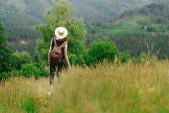 有背包的时髦的行家妇女看惊人的森林 库存图片
