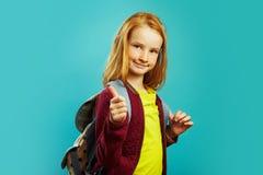 有背包的正面学童在他的肩膀后显示他的拇指,显示积极态度对研究,站立  免版税库存照片