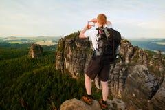 有背包的游人在两只手做与手指的框架 有大背包立场的远足者在森林上的岩石观点 免版税库存照片