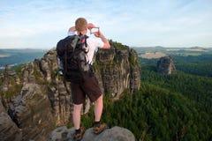 有背包的游人在两只手做与手指的框架 有大背包立场的远足者在森林上的岩石观点 免版税库存图片