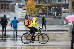 有背包的男性骑自行车者在街道上 库存照片