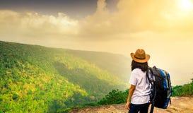 有背包的站立观看森林和天空的美丽的景色年轻旅行的妇女和帽子在山峭壁的上面 免版税库存照片