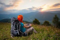 有背包的红发夫人在日落的山 免版税图库摄影