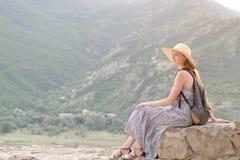 有背包的美丽的女孩在一个宽帽子坐山的背景 免版税图库摄影