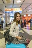 有背包的美丽的旅游女孩和继续在int的行李 免版税库存照片