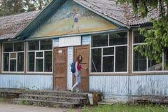 有背包的美丽的红色头发妇女游人在军用餐具附近的门在被放弃的先驱阵营的 免版税库存图片