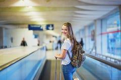 有背包的美丽的年轻旅游女孩和在国际机场继续行李 免版税图库摄影
