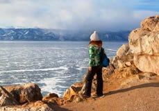 有背包的自由愉快的妇女享受冻结的贝加尔湖表面的看法  冬天旅游业概念 库存照片