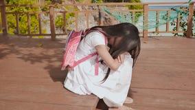 有背包的菲律宾女小学生女孩是坐和哭泣在热带海岸哀伤的心情附近 影视素材