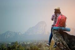 有背包的行家亚裔少女享受在高峰山的日落 旅行生活方式冒险概念 免版税图库摄影