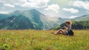 有背包的行家在惊人的风景的女孩和照相机在有雾的山峰顶  免版税库存照片