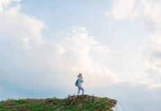 有背包的行家女孩享受在小山峰顶的日落  免版税库存图片
