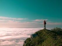 有背包的被定调子的图象妇女站立在峭壁和看日出边缘反对蓝天 免版税库存图片