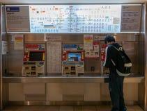 有背包的身份不明的人买从自动化的票分与的机器的火车票  免版税库存照片