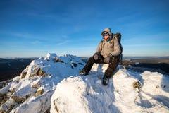 有背包的远足者和有休息坐一个积雪的岩石的上面在冬天山的 免版税库存照片