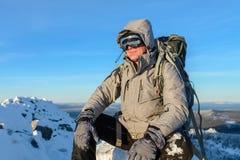 有背包的远足者和有休息坐一个积雪的岩石的上面在冬天山的 免版税库存图片