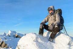有背包的远足者和有休息坐一个积雪的岩石的上面在冬天山的 库存图片
