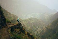 有背包的远足者在山上面 高山范围深深一个难以置信的全景视图的岩石地形和 免版税库存照片