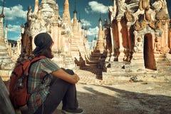 有背包的远足者在缅甸坐并且看起来佛教stupas 免版税库存图片