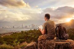 有背包的远足者坐在山顶部享用看法coa的 免版税库存图片