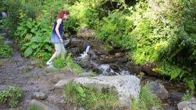 有背包的远足者妇女走在山的一串森林足迹的在背景瀑布 高涨 冒险 股票录像