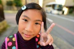 有背包的逗人喜爱的亚裔女孩在日本 库存照片