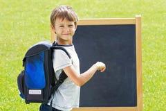 有背包的逗人喜爱的小男孩在室外的黑板 库存照片