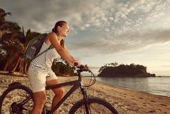 有背包的骑自行车者女孩享受美丽的海岛的看法  免版税库存照片