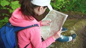 有背包的年轻严肃的旅游妇女看对她的地图和举眼睛检查与地方地形的 股票录像
