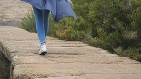 有背包的年轻女性游人走在石足迹的室外 努力去做在岩石地面的妇女的腿在美丽 股票录像