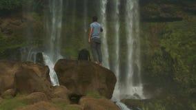 有背包立场的人在岩石由瀑布喝水 股票视频