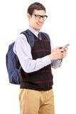 有背包键入的微笑的学员在电话的sms 图库摄影