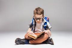 有背包阅读书的小男孩在瑜伽姿势 库存图片