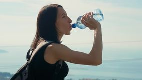有背包饮用水的妇女旅客从瓶 健康在自然远足的远足者女孩饮用水 股票录像