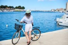 有背包骑马城市自行车的少妇在海附近 库存照片