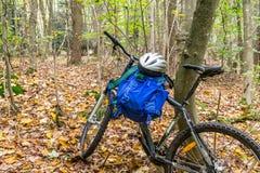 有背包andhelmet的登山车在森林里 库存照片
