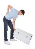 有背部疼痛举的金属箱子的人 库存图片
