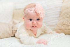 有胖的穿白色衣裳的面颊和大蓝眼睛的甜矮小的婴孩和与说谎在床上的花的桃红色带 免版税图库摄影