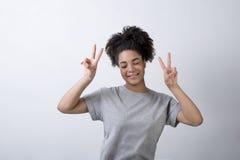 有胜利标志的愉快的妇女 免版税库存图片