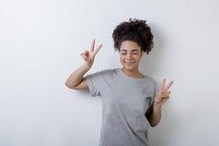 有胜利标志的愉快的妇女 免版税库存照片