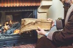 有胡子佩带的浴巾的人投入注册灼烧的壁炉 免版税库存照片
