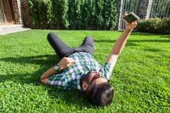 有胡子和时尚发型的一个年轻时尚中东人在一棵草说谎在采取selfie的公园 库存图片