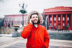 有胡子和红色夹克的年轻人在敞篷学生在他的手上使用手机,举行在头附近,谈话在电话机智 免版税库存照片