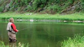 有胡子和长发的一个中年人将用假蝇钓鱼在山河 一套防水衣服的一位渔夫站立 股票录像