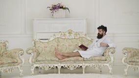有胡子和髭的人享受早晨,当说谎在豪华沙发时 人困在浴巾,喝咖啡,读书 股票录像