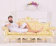 有胡子和髭的人在豪华沙发时享受早晨,当放置 困笑容的人在浴巾,饮料 图库摄影