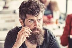 有胡子和髭的人坐室外在咖啡馆大阳台 镇静面孔的有胡子的人看起来哀伤和麻烦 行家与 库存图片